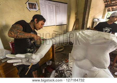 BALI, INDONESIA - FEB 24, 2016: Unidentified local people build Ogoh-ogoh statues for the Ngrupuk parade, which takes place on the eve of Nyepi day. Nyepi is a public holiday in Indonesia.
