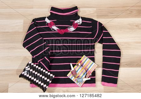 Winter sweater and accessories arranged on the floor. Woman pullover with colorful pink accessories sunglasses and nail polish.