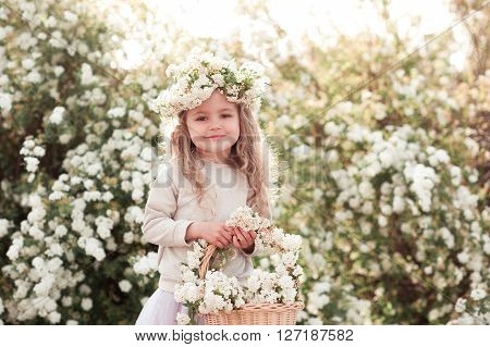 Smiling blonde kid girl holding basket with flowers outdoors. Looking at camera. Wearing floral wreath.