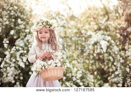 Cute kid girl 3-4 year old wearing stylish clothes and holding basket with flowers outdoors. Childhood.