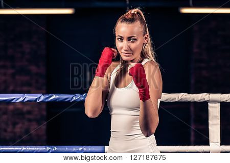 Portrait of young beautiful boxer woman ready to kick with red boxing bandage on hands in gym. Strong hand and fist, ready for fight and active exercise.