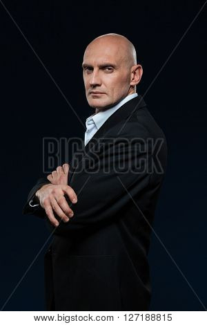 Mature businessman standing with arms folded on dark background