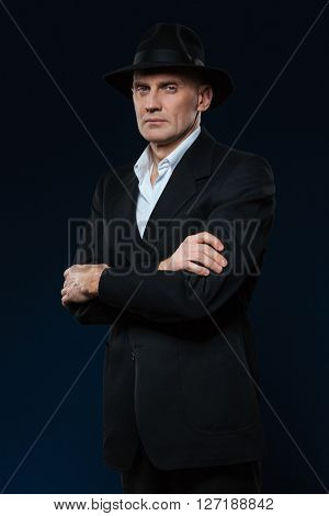 Confident businessman standing with arms folded on black background and looking at camera