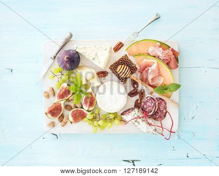 Wine and snack set. Figs, grapes, nuts, cheese variety, meat appetizers and herbs on light blue background, top view