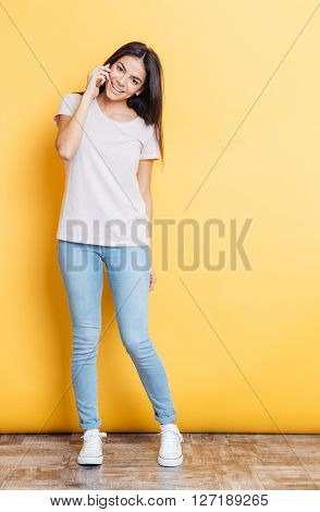 Full length portrait of a pretty woman talking on the phone and looking at camera over yellow background