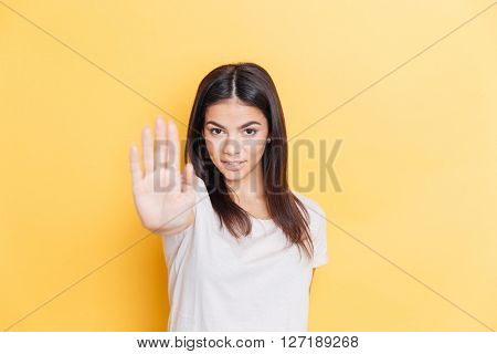 Portrait of a cute woman showing stop gesutre with palm over yellow background