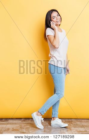 Full length portrait of a laughing woman talking on the phone and looking at camera over yellow background