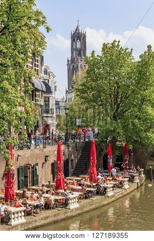 Utrecht, Netherlands - May 6: There are duplex embankments of the city with a cafe at the edge of the canal and the cathedral at a sunny day Domtoren May 6, 2013 in Utrecht, Netherlands.