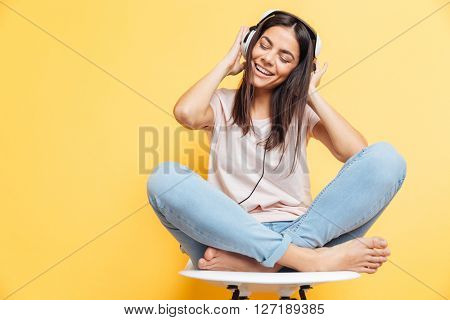 Cheerful woman listening music in headphones over yellow background