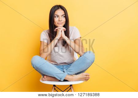Happy cute woman sitting on the chair and looking away over yellow background