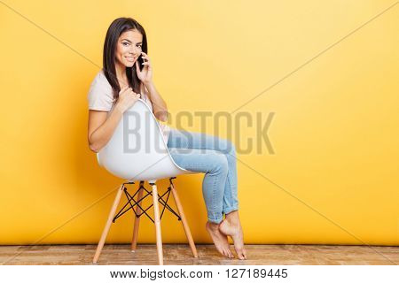 Happy beautiful woman sitting on the chair and talking on the phone over yellow background