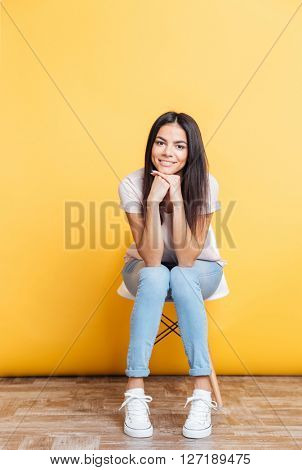 Smiling pretty woman sitting on the chair over yellow backgorund