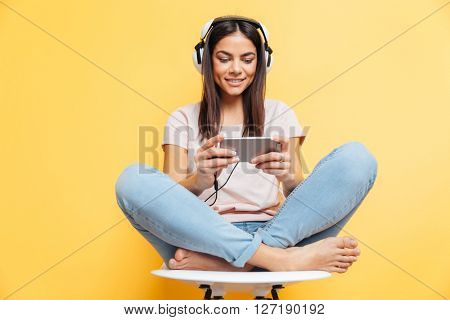 Happy woman listening music in headphones and using smartphone over yellow background