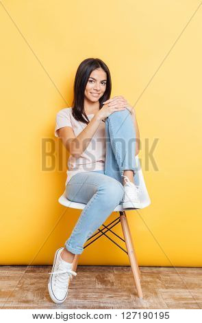 Full length portrait of a happy attractive woman sitting on the chair over yellow background