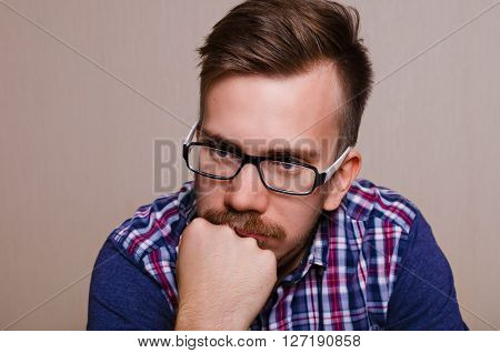 Man in dreams. Guy thinking. Portrait of man in glasses with a beard and mustache with his head propped on his hand