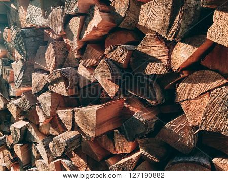 Photo of dry chopped firewood logs in a pile. Outdoors photo.