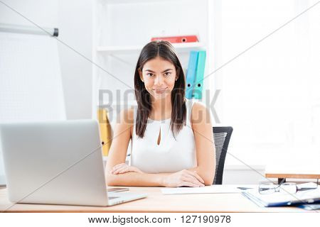 Smiling businesswoman sitting at her workplace in office and looking at camera
