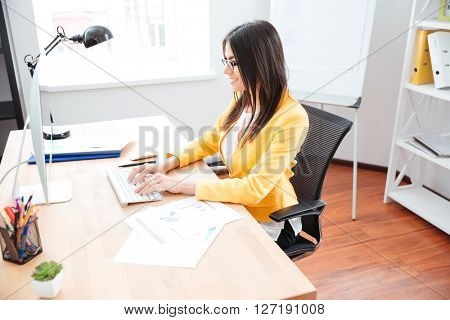 Cheerful businesswoman using computer in office