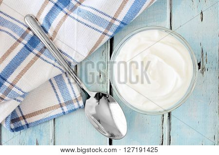 Greek Yogurt In A Bowl, Downward View With Cloth And Spoon On A Rustic Soft Blue Wood Background