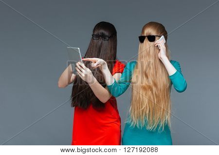 Two playful young women covered face with long hair and using mobile phone and tablet over grey background