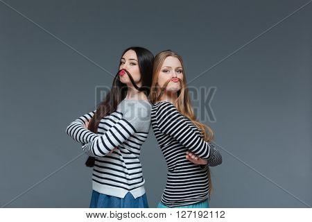 Two funny young women standing with arms crossed and making moustache with their hair over grey background