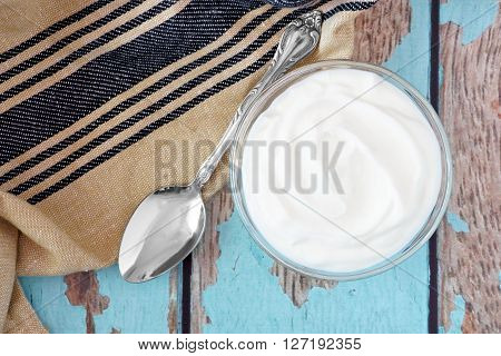 Greek Yogurt In A Bowl, Overhead View With Cloth And Spoon On A Rustic Blue Wood Background