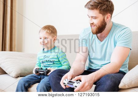 Happy cute son sitting on couch and playing computer games  with his father at home