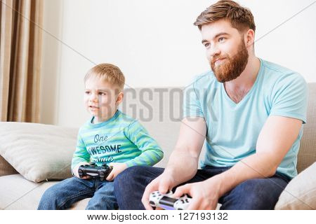 Sad unhappy dad and son playing computer games at home