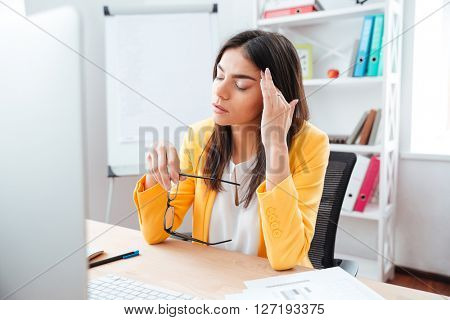 Businesswoman sitting with headache at her workplace in office