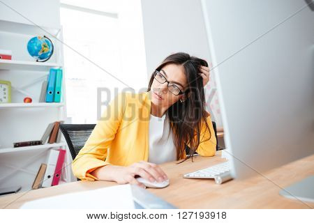 Pensive businesswoman sitting at the table with computer and looking away in office