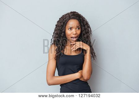 Stressed afro american woman screaming on gray background