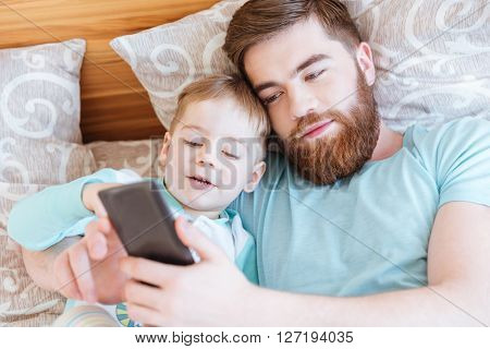 Portrait of father lying on bed with his little son and using mobile phone