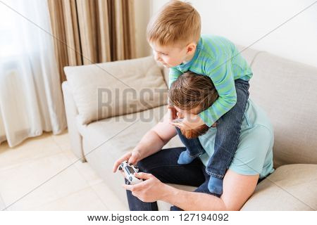 Handsome young man sitting on sofa and playing computer games while his little son covering his eyes