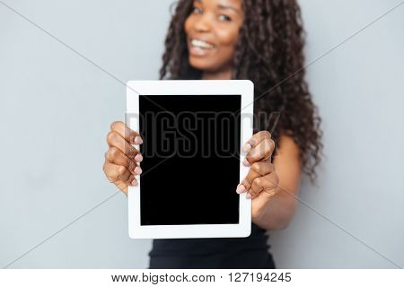 Smiling afro american woman showing blank tablet computer over gray background. Focus on tablet computer