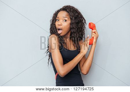 Amazed afro american woman holding retro phone tube and covering microphone over gray background