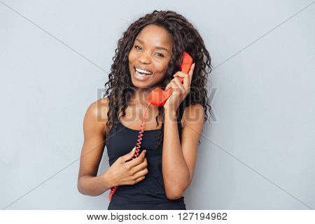 Happy afro american woman talking on retro phone tube over gray background