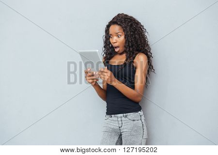 Shocked afro american woman using tablet computer over gray background