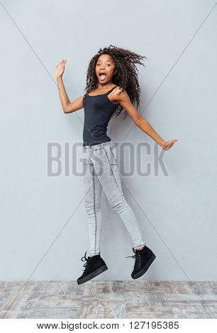 Full length portrait of a funny afro american woman jumping on gray background