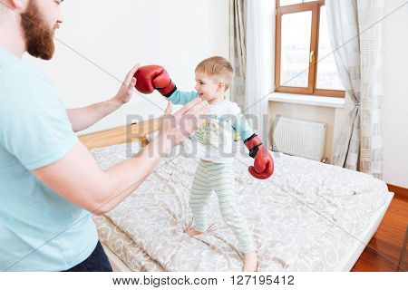 Smiling little boy in red boxing gloves standing on bed and playing with his dad at home