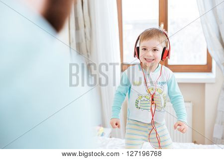 Smiling cute little boy in red headphones standing on bed and listening to music