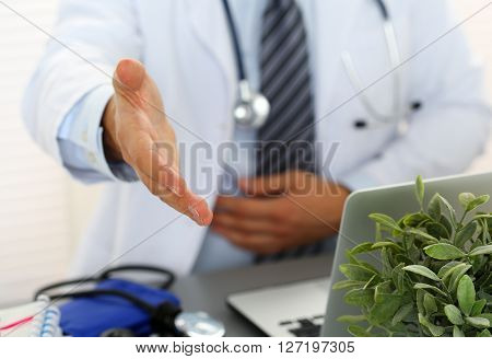 Male medicine doctor offering hand to shake in office closeup. Greeting and welcoming friend introduction or thanks gesture. Tests advertisement concept. Physician ready to examine patient