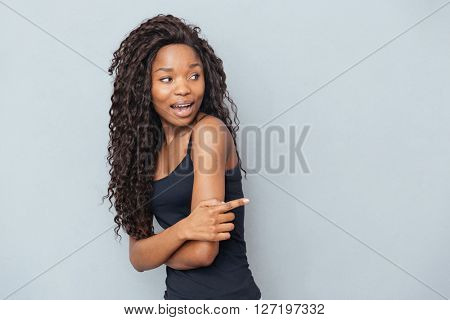 Afro american woman pointing finger away over gray background