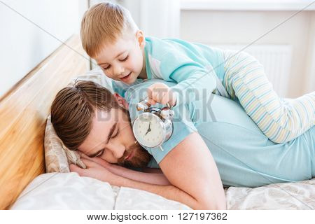 Cute little son holding alarm clock near sleeping father ear at home