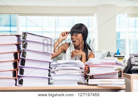 Shocked afro american businesswoman sitting at the table with many work in office