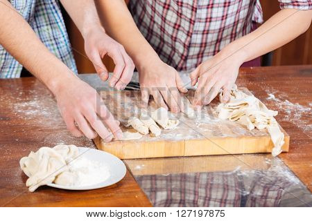 Hands of young couple kneading dough and cooking together