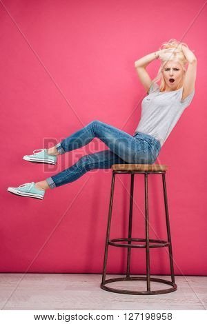 Amazed blonde woman sitting on the chair and looking at camera over pink background