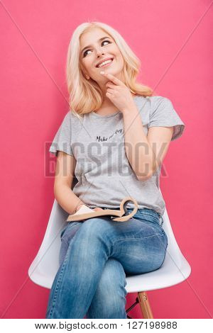 Happy thoughtful woman sitting on the chair with magazine and looking away over pink background