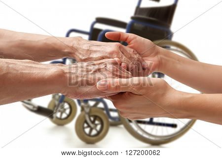 Hands of an elderly man holding the hand of a woman on wheelchair background