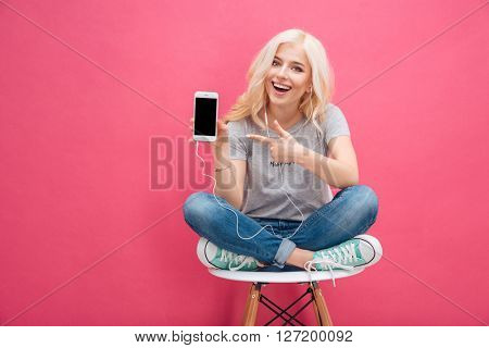 Cheerful woman sitting on the chair and showing blank smartphone screen over pink background