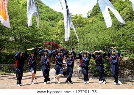 KAGAWA, JAPAN - MAY 22, 2016: Excursion of an Japanese high school girls, they are poseing pleasant and fun in a row at Fudonotaki- park, Kagawa, Japan.